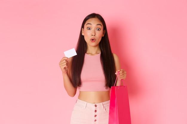 Beauty-, mode- und lifestyle-konzept. amüsiertes hübsches asiatisches mädchen, das tasche und kreditkarte hält, verlockend, etwas zu kaufen, guten preis zu sehen, wow zu sagen, beeilen sie sich, um kauf zu machen, rosa wand