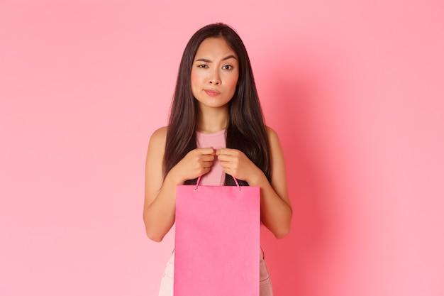 Beauty-, mode- und lifestyle-konzept. das porträt eines skeptischen und unbeschwerten asiatischen brünettenmädchens erhält ein geschenk, ist aber unzufrieden damit, hält eine einkaufstasche und verzieht das gesicht enttäuscht.