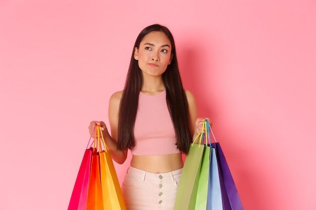 Beauty-, mode- und lifestyle-konzept. porträt eines unentschlossenen hübschen asiatischen mädchens mit einkaufstüten, schmollen während der wahl, kaufentscheidung oder nicht, blick in die obere linke ecke.