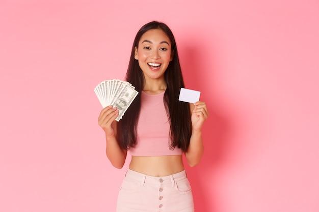 Beauty-, mode- und lifestyle-konzept. taille der jungen schönen asiatischen frau im trendigen outfit, das kreditkarte und geld zeigt, lächelnd, als erklären, wie man kauf macht, rosa wand.