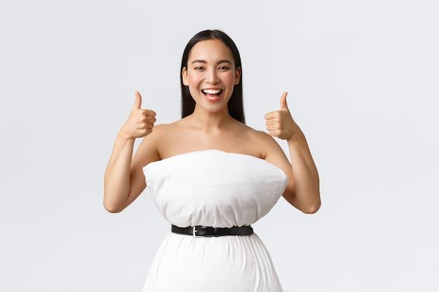 Beauty-, mode- und social-media-konzept. glücklich lächelnde asiatische frau, die spaß hat, an der internet-kissenherausforderung teilzunehmen, kleid aus kissen und gürtel zu machen, die sich um abfall schmiegen, daumen hoch zeigen