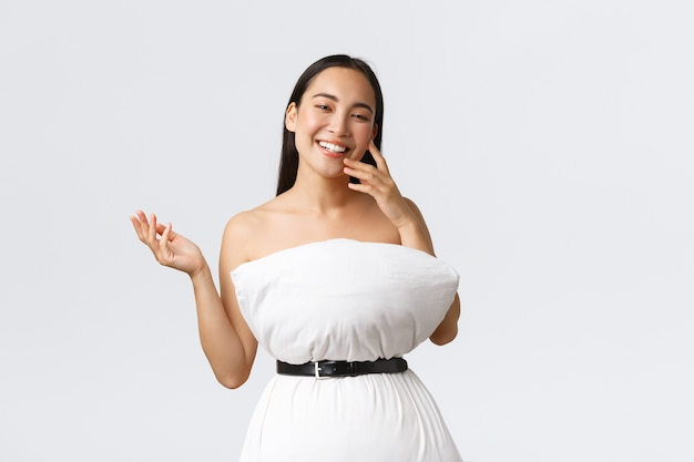 Beauty-, mode- und social-media-konzept. ziemlich glückliche asiatische frau lacht und zeigt ihr neues outfit aus kissen und gürtel, posiert im kissenkleid über weißer wand