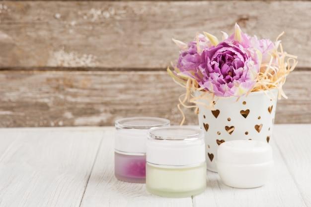 Beauty-produkte, kosmetik, brennende kerze und lila tulpen