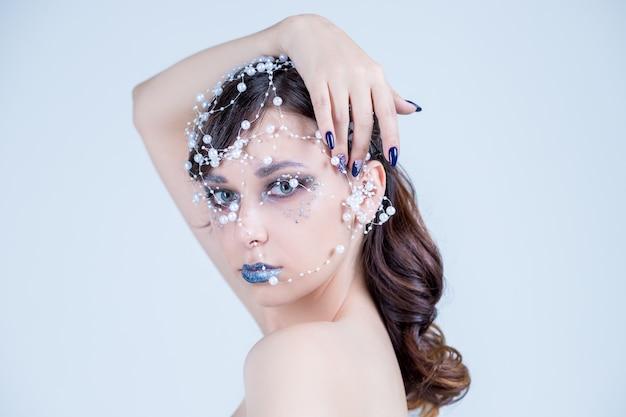 Beauty queen nahaufnahme porträt modell. perlen, kristalle halskette silber halsband. frisur brünette haarschleife. magischer kalter winter kommt. winter kreatives make-up und dekoration mit perlen.