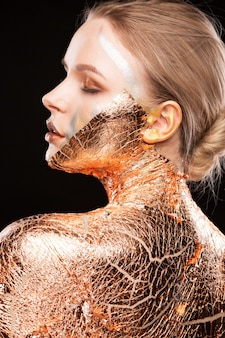 Beauty-shooting eines glamourösen blonden mädchens mit kreativem make-up und goldener folie auf schultern, gesicht und rücken