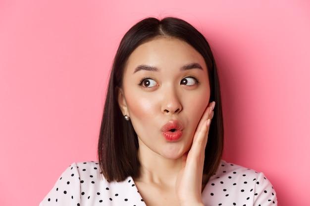 Beauty- und lifestyle-konzept. nahaufnahme der koketten asiatischen frau, die verblüfft links schaut, auf einkaufsangebot starrend, über rosa stehend. Premium Fotos