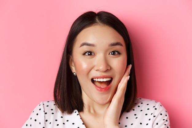 Beauty- und lifestyle-konzept. nahaufnahme einer überraschten und glücklichen asiatischen frau, die erstaunt in die kamera starrt, ungläubig nach luft schnappt und über rosafarbenem hintergrund steht.