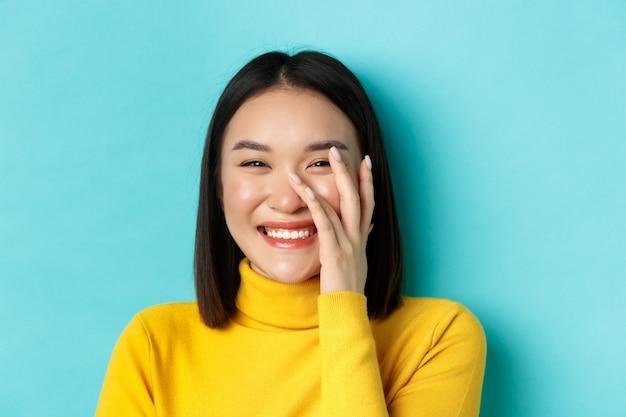 Beauty- und make-up-konzept. nahaufnahme einer schönen asiatischen frau, die errötet und lacht, leuchtende gesunde haut berührt, glücklich lächelt und auf blauem hintergrund steht.
