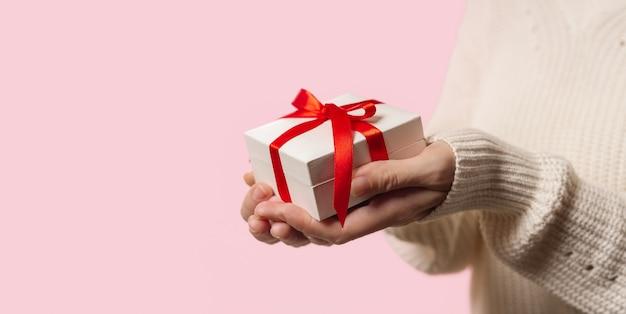 Beauty woman hände halten geschenkbox mit roter schleife auf rosa
