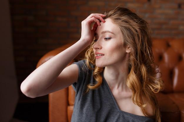 Beauutiful junge frau mit rotem haar onloft backsteinmauerhintergrund