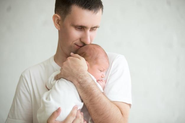 Bebé dormido en los brazos de su padre mientras su padre le besa la cabeza