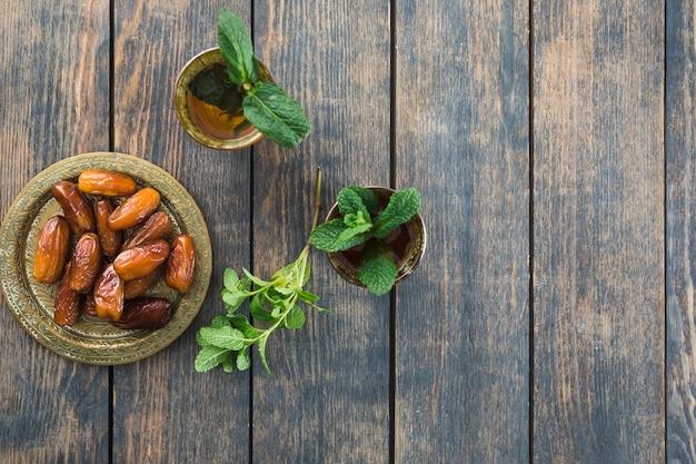 Becher des getränks nahe trockenfrüchten auf saucer