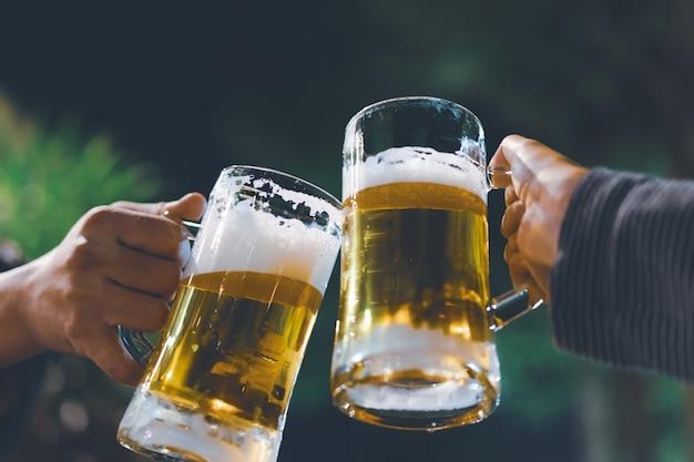 Becher des kalten handwerksbieres oben, freunde trinken bier zusammen