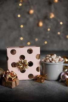 Becher für modell nahe weihnachtsbaum und geschenkboxen