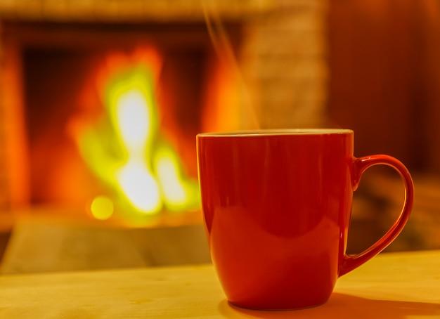Becher für tee oder kaffee, auf hintergrund des gemütlichen kamins, weicher fokus.