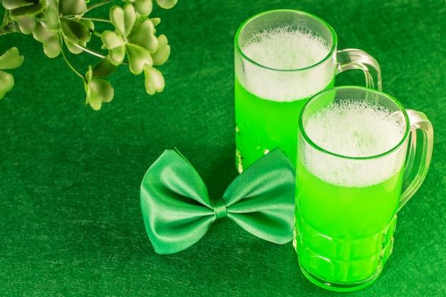 Becher grünes bier mit blättern des kleeblatts auf grün