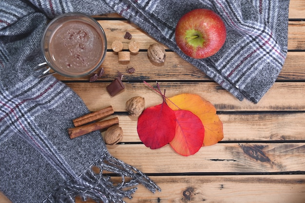 Becher heiße schokolade mit schal und rotem apfel im winter und auf einem holztisch