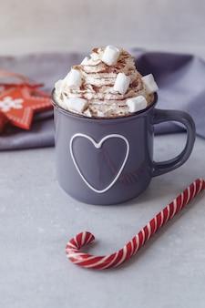 Becher heiße schokolade mit schlagsahne, eibischen und rotem lutscher auf einem grauen hintergrund. heißes wintergetränk