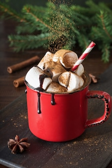 Becher heiße schokolade und kakao mit marshmallows mit weihnachtstannenzweigen auf holzbrett