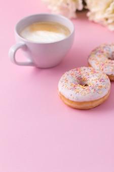 Becher heißer cappuccino mit zwei schaumgummiringen auf rosa