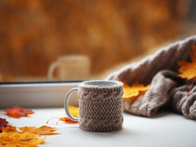Becher heißer kaffee mit gestrickter warmer strickjacke und herbstlaub auf dem fenster im haus. hygge-konzept