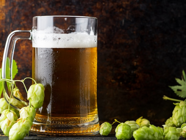 Becher hüpfte helles bier auf einem dunklen rostigen hintergrund mit grünen hopfen