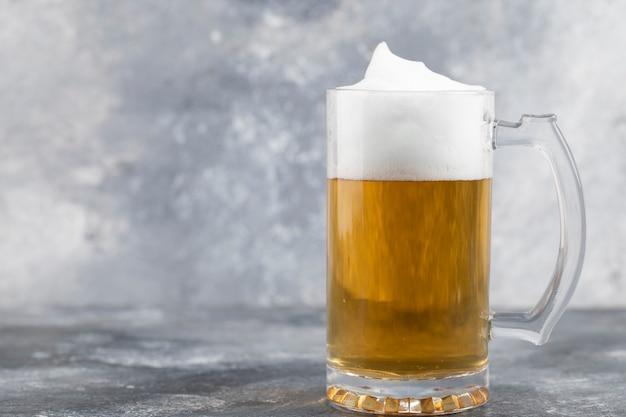Becher kaltes schaumiges bier auf marmoroberfläche gestellt