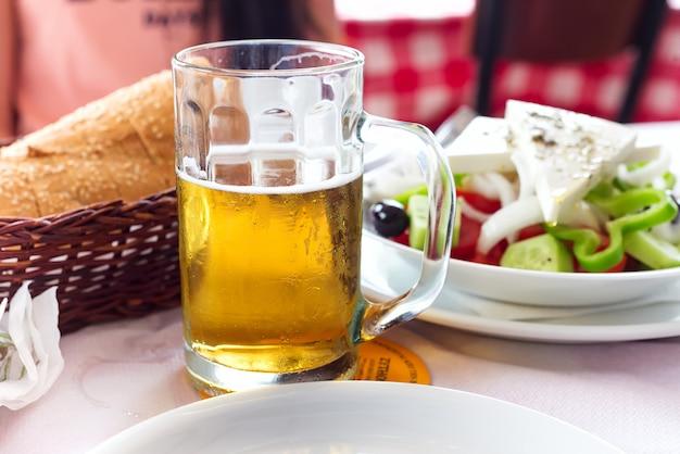 Becher mit bier auf dem hintergrund eines äußeren straßencafés