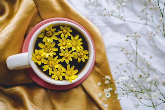 Becher mit gelben blumen auf einem goldenen satinstoff.