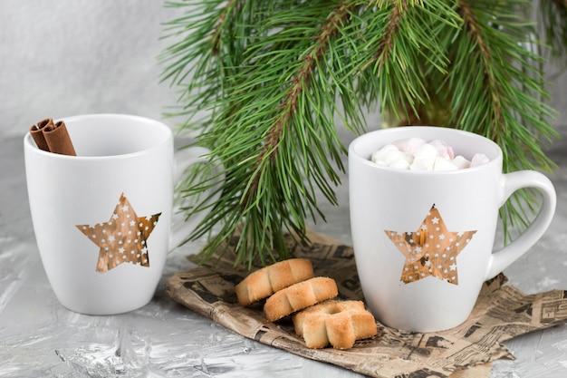 Becher mit getränken und plätzchen nähern sich immergrünem grauem konkretem hintergrund der weihnachtsbaumaste