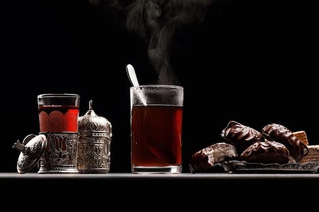 Becher mit heißem tee, von dem es dampf gibt, auf einem dunklen hintergrund mit marshmallows und marmelade. tee mit süßigkeiten. östliche tradition.