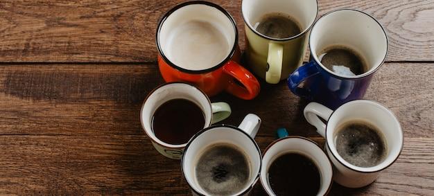 Becher mit kaffee auf hölzernem hintergrund