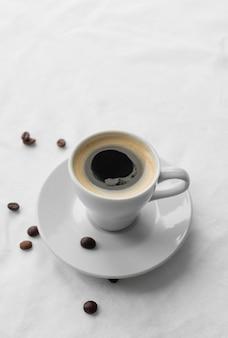 Becher mit kaffee und kaffeebohnen daneben