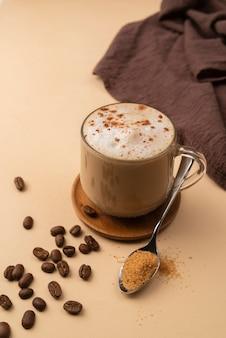 Becher mit kaffee und kaffeebohnen und pulver daneben