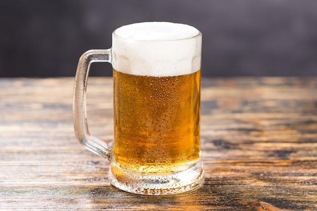 Becher mit kaltem, hellem bier auf einem rustikalen holztisch mit kopierraum.