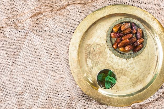 Becher mit pflanzenzweigen und trockenfrüchten auf tablett