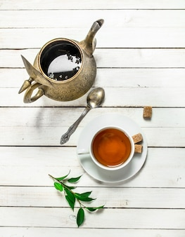 Becher mit schwarzem tee.