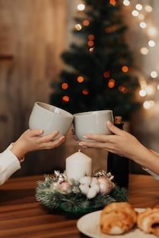 Becher mit tee auf dem hintergrund eines weihnachtsbaumes. neujahr und weihnachten. geschenke