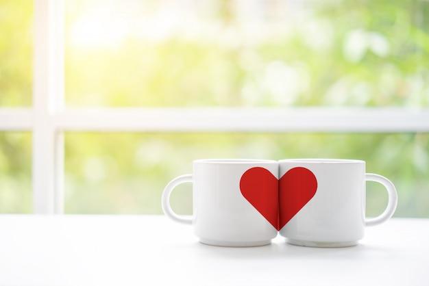 Becher tasse kaffee oder tee für den flitterwochenhochzeitsmorgen mit zwei liebhabern in der kaffeestube