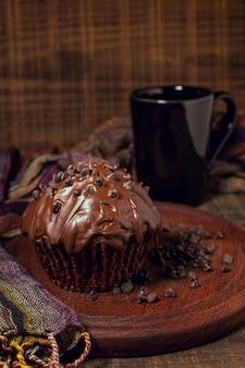 Becher und muffin der heißen schokolade auf hölzernem brett