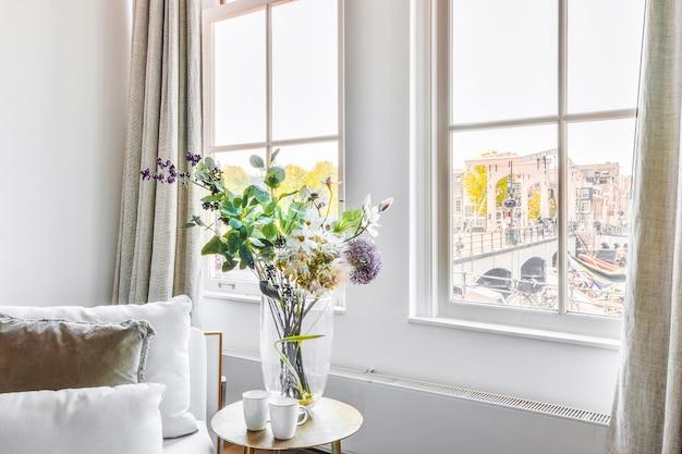 Becher und vase mit blumenstrauß auf tisch in der nähe von sofa und fenstern in hellem wohnzimmer in wohnung gestellt