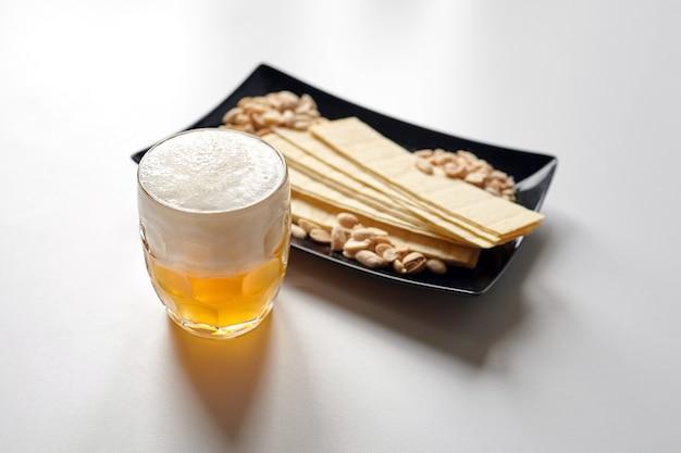 Becher ungefiltertes leichtes weizenbier mit biersnacks auf weißem tisch