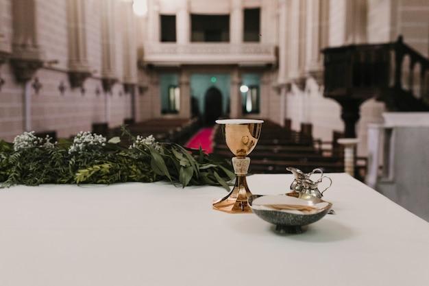 Becher wein auf tabelle während einer hochzeitszeremonie-hochzeitsmasse. religion-konzept. ornamente der katholischen eucharistie zur feier der eucharistie