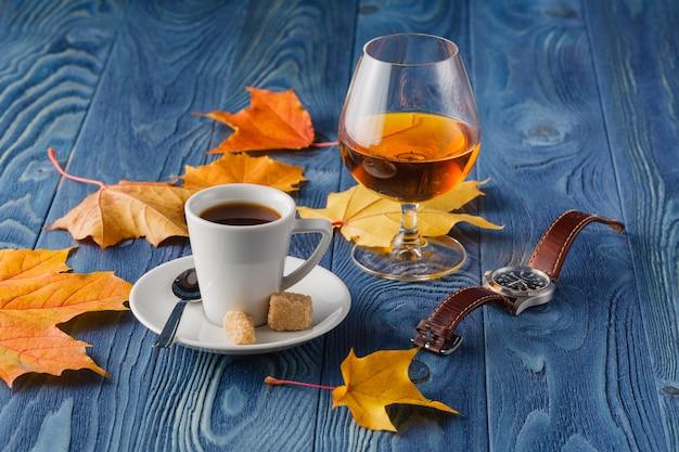 Becher weinbrand und schale heißer coffeeon hölzerne alte gegenspitze