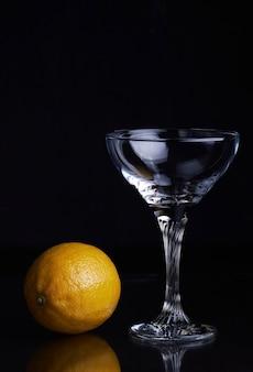 Becherglas mit gin tonic cocktail und zitrone auf isoliertem schwarz