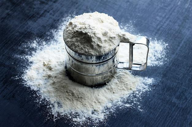 Bechersieb wird mit mehl gefüllt, mehl wird herum auf dunklen hölzernen hintergrund zerstreut.