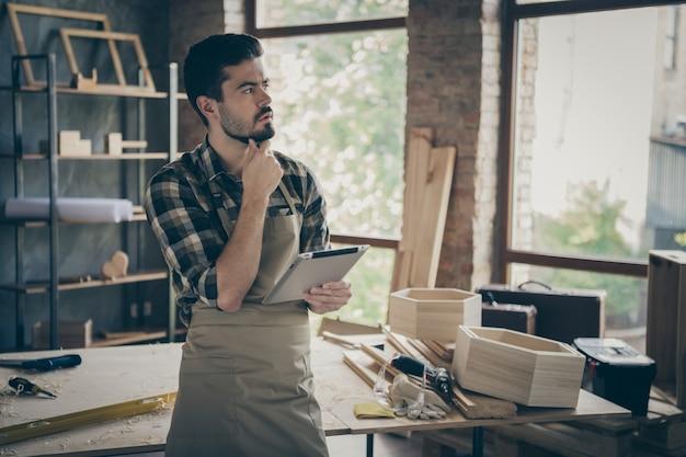 Bedacht nachdenklich hartholz vorarbeiter professionelle arbeiter verwenden tablet denken entscheiden kunden wählen reparatur restaurierungsaufträge angebote in der garage zu hause