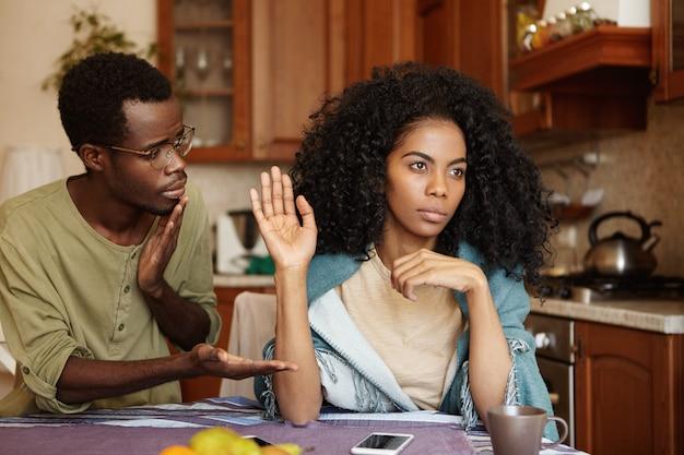 Bedauerlicher schuldiger junger afroamerikanischer mann in gläsern, der seiner wütenden freundin als zeichen der versöhnung nach einem ernsthaften streit hand anbietet, aber die frau scheint alle entschuldigungen und ausreden abzulehnen