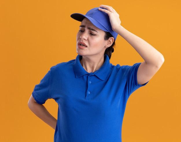Bedauern der jungen lieferfrau in uniform und mütze, die die hand hinter dem rücken und auf dem kopf hält und zur seite schaut