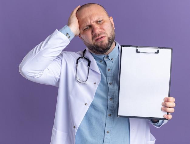 Bedauern eines männlichen arztes mittleren alters, der ein medizinisches gewand und ein stethoskop trägt und die zwischenablage zur kamera zeigt, die die hand auf dem kopf hält und auf die seite schaut